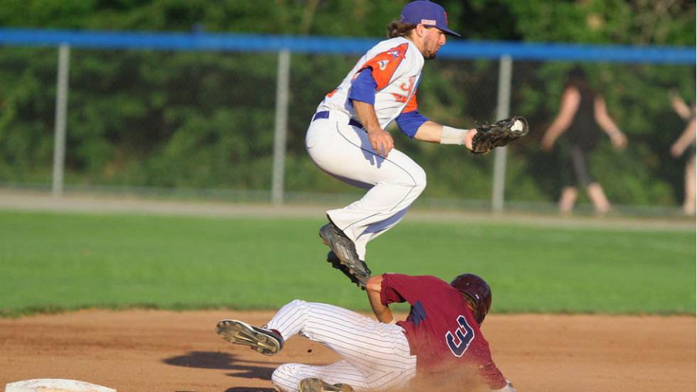 Ryne Birk catches a throw as Cotuit's Jeren Kendall slides underneath him in Monday's playoff game.